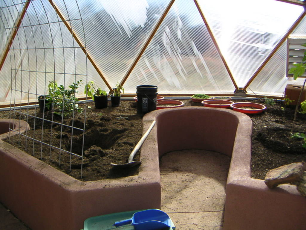 stucco raised beds with keyholes in Growing Dome greenhouse