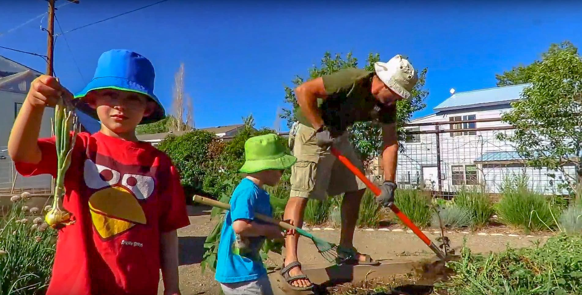 Andrew and his sons working in the community garden next to the greenhouse