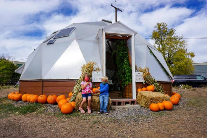 kids with pumpkins outside dome greenhouse in Golden Colorado